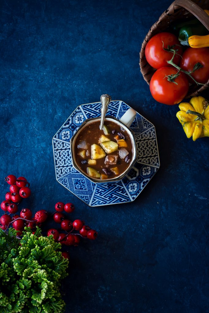 This Vegan Chilli Soup offers cozy comfort of hearty vegetables, triple bean blend, herbs & spices, and is my go-to meal during the winters! #foodphotography #vegan #veganchilli #winter #comfortfoods