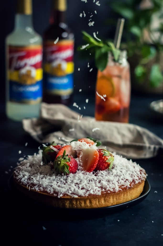 Moist and soft VEGAN Coconut Cake topped with strawberry jam, coconut flakes and doused in delicious coconut syrup. #ad #AToraniBrunch #ToraniFlavor #foodphotography #dessert