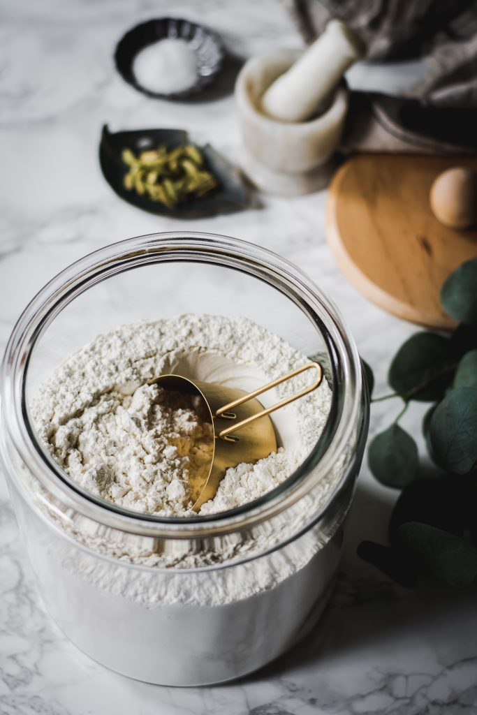 Glass container of flour with measuring cup