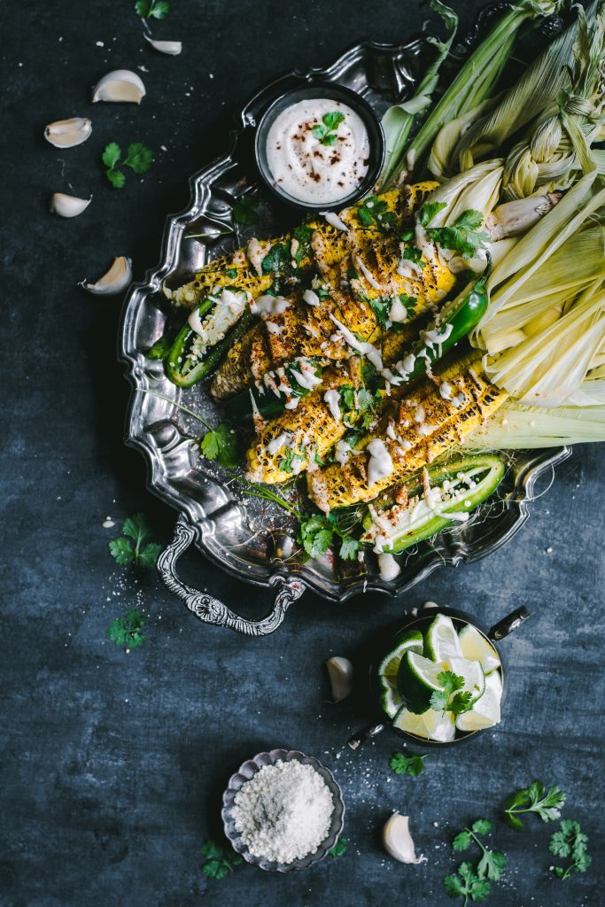 VEGAN Elotes - A plant based twist on the classic Mexican Street corn - Succulent sweet corn grilled to perfection, doused in a flavorful cashew crema and rolled in more cashews for that touch of decadence. #vegan #foodphotography #elotes #plantbased