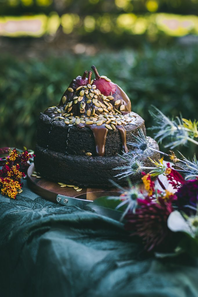 Rich and decadent Vegan Chocolate Pumpkin Spiced Cake topped with pears poached in red wine and chocolate ganache.