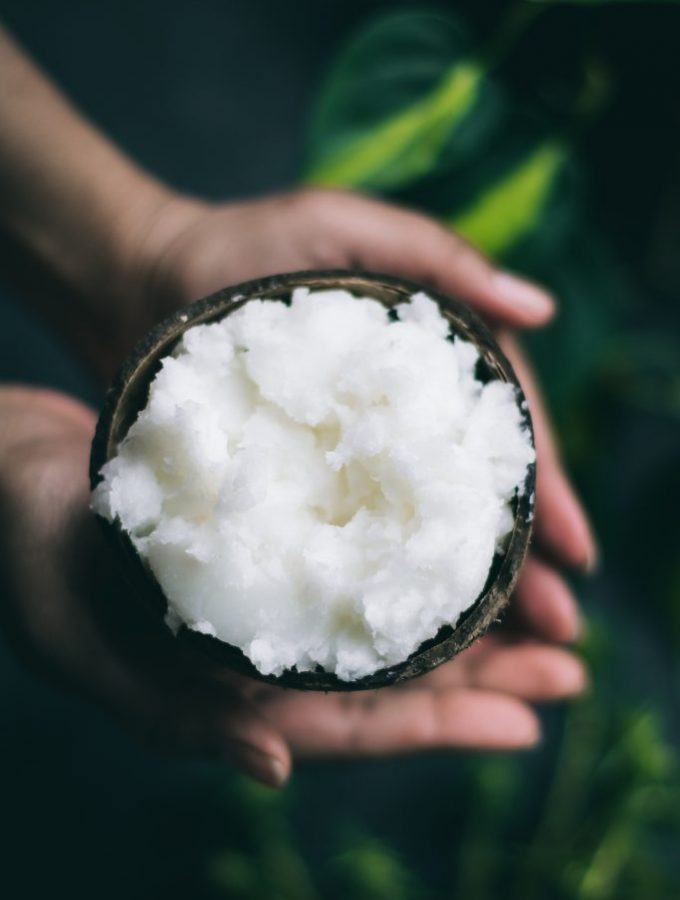 Coconut oil in coconut shell on a background of green