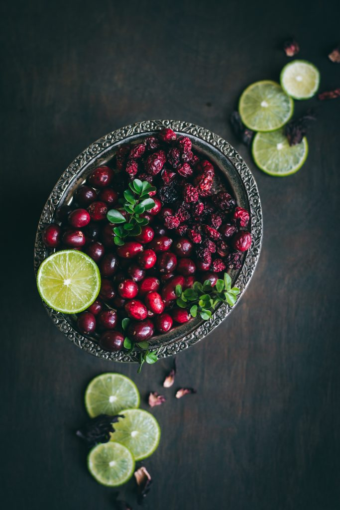 A plate of cranberries both fresh and dried with lemon slices and dried hibiscus