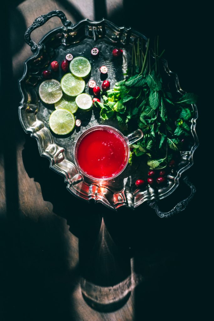 An overhead shot of a cup of Simple Cranberry Hibiscus Tea on a silver platter with ingredients