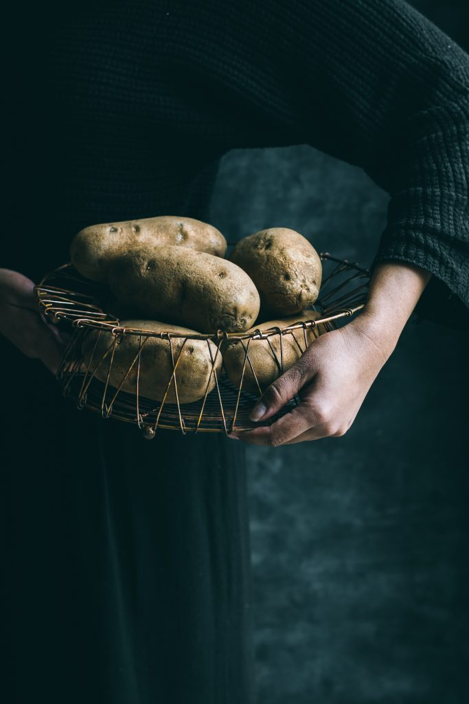 Woman holding basket of russet potatoes