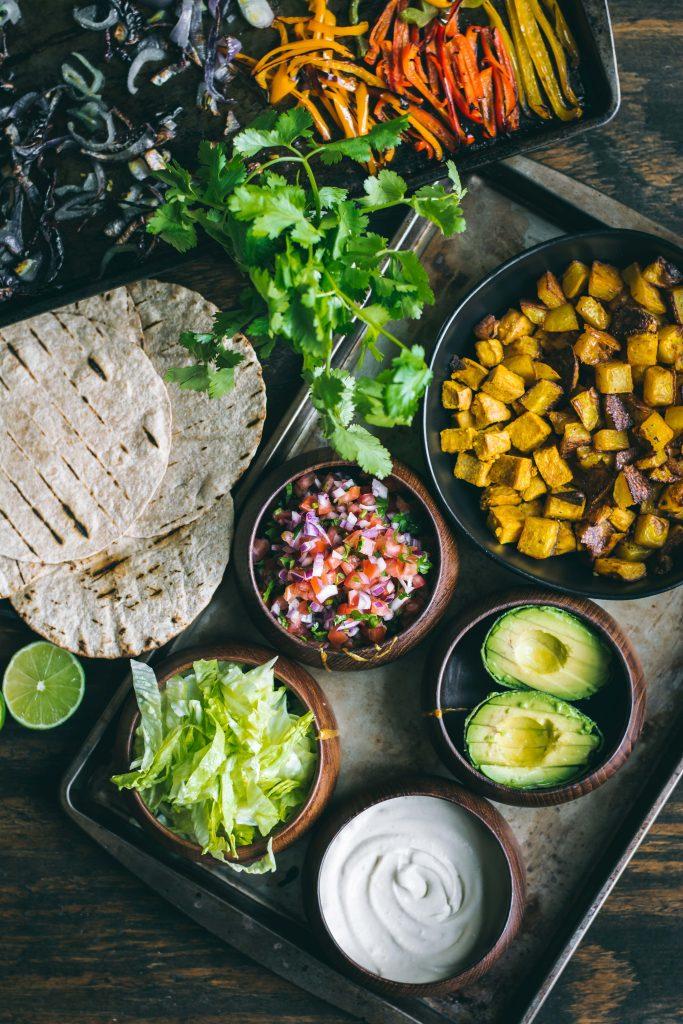 VEGAN Sheet Pan tacos with crispy potatoes, tofu, onions, peppers, avocado and cashew queso.