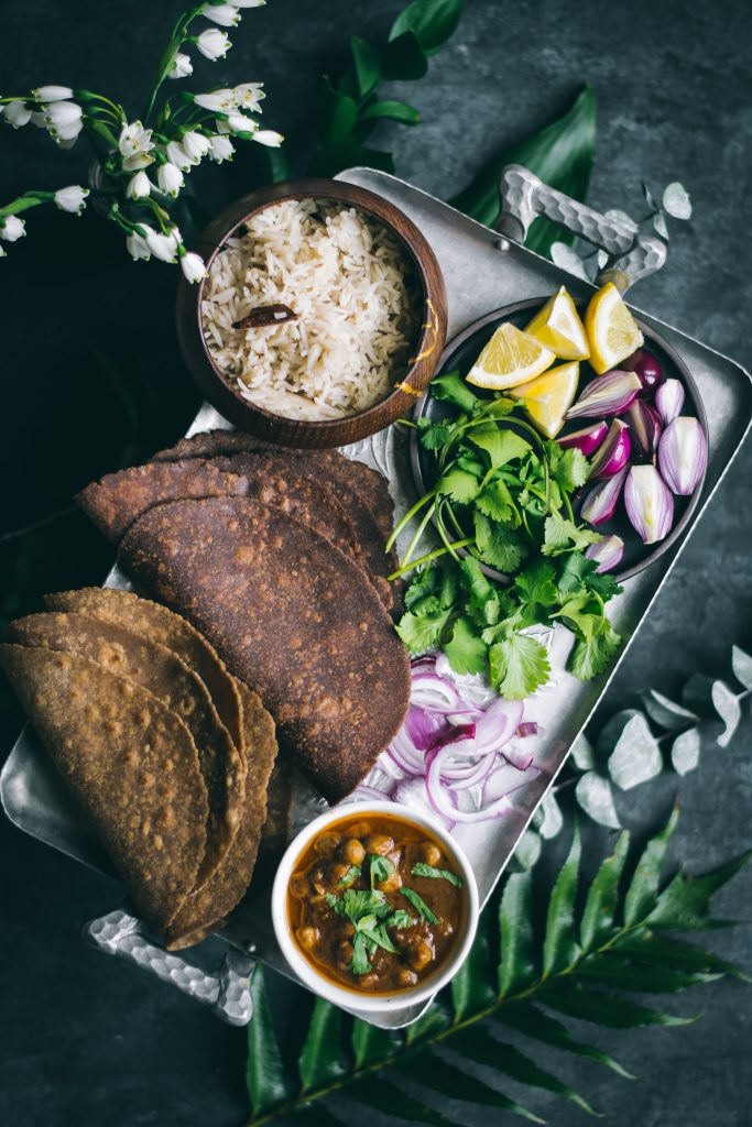 Teff Rotis on a platter with rice, curry and vegetables