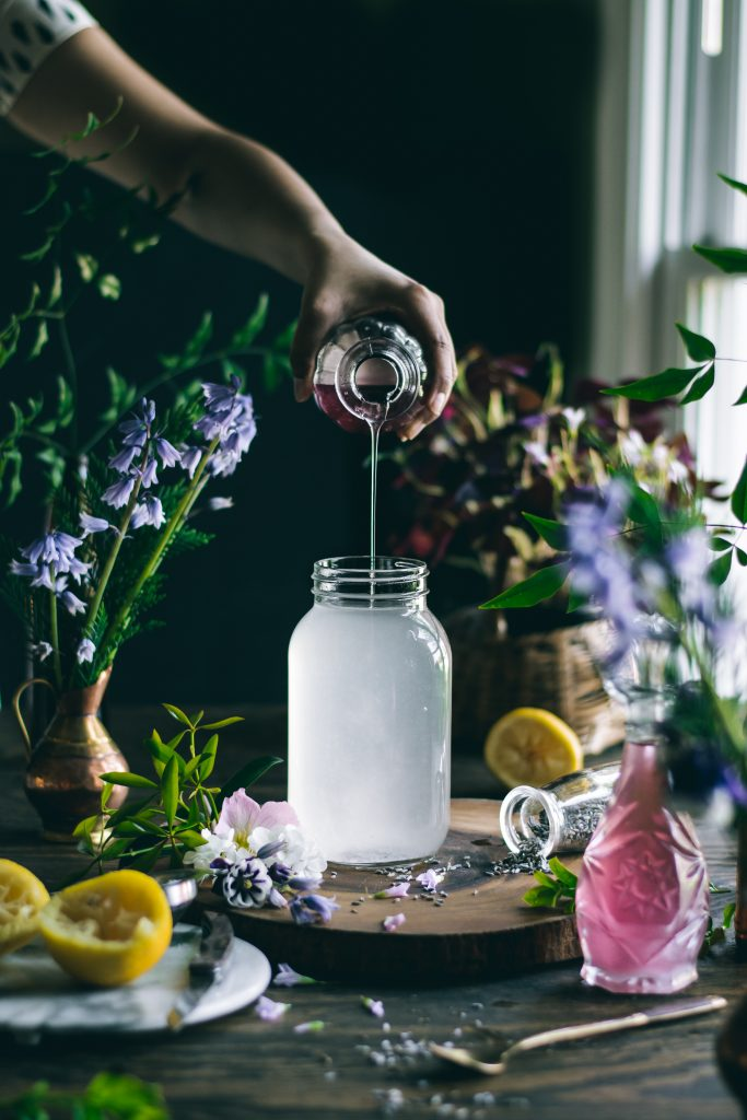 Pouring Lavender Syrup into a jar of lemonade. Every sip of this fragrant, 5 ingredient Lavender Lemonade will remind you of the floral beauty of Spring.