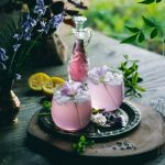 Lavender Lemonade in glasses with a primrose floral garnish. Every sip of this fragrant, 5 ingredient Lavender Lemonade will remind you of the floral beauty of Spring.