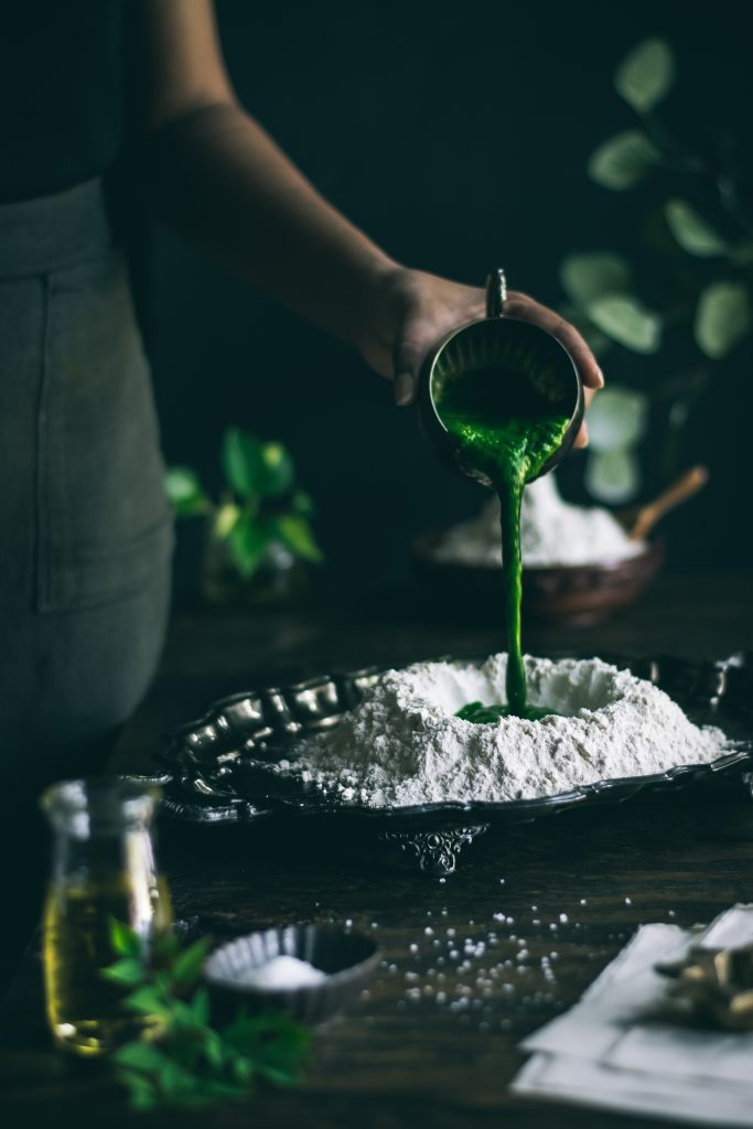 Pouring Spinach puree into Flour well for making Spinach Roti