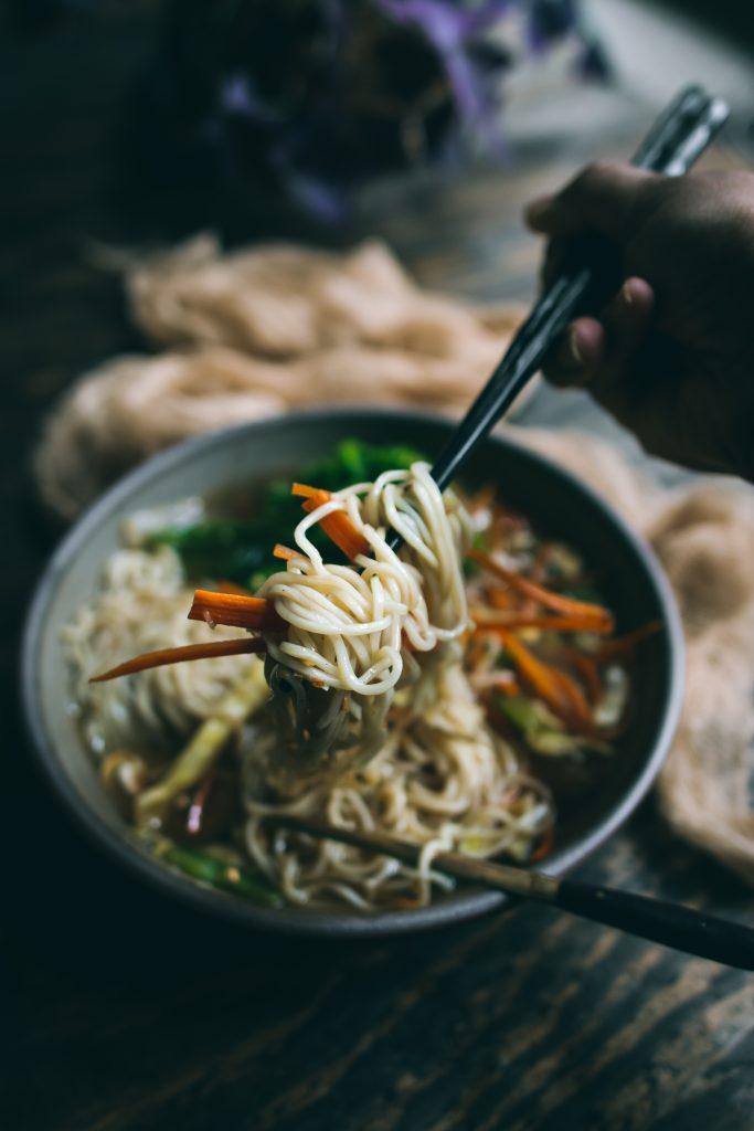 Chopsticks lifting noodles from bowl