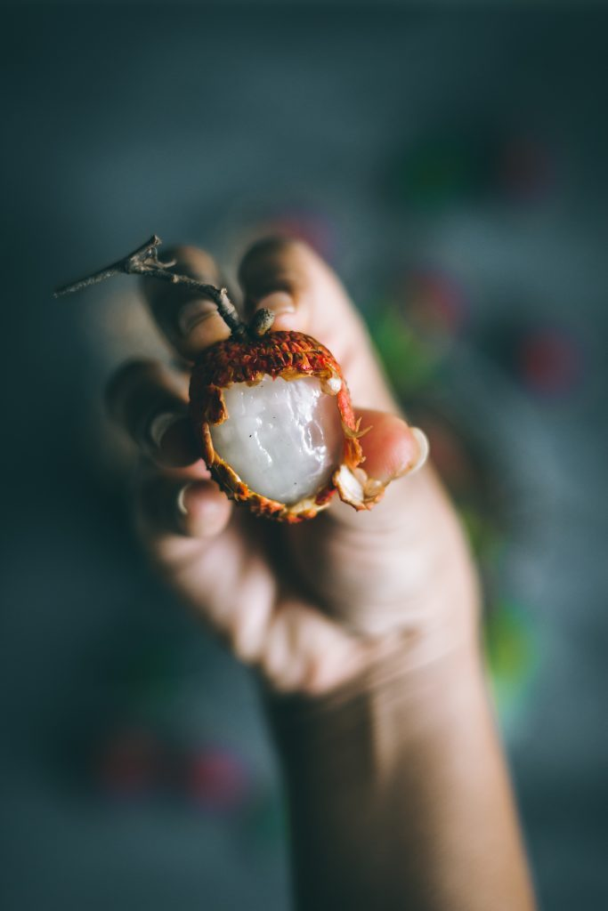 Hand holding Lychee with skin peeled off