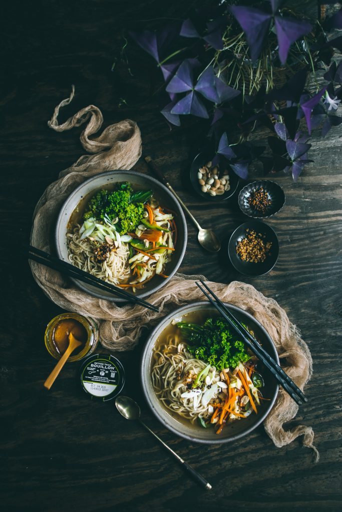 Flatlay of VEGAN Lemongrass Ramen in two bowls, with condiments and cutlery