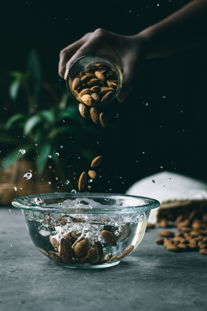 Pouring Almonds into a bowl of water with a splash
