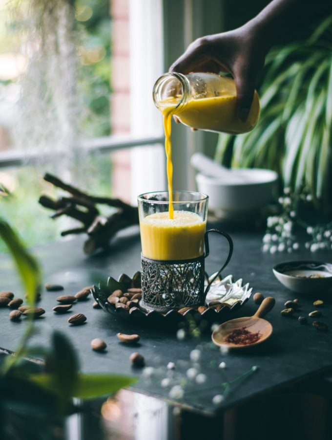 Pouring saffron and cardamom infused almond milk into a Russian tea glass