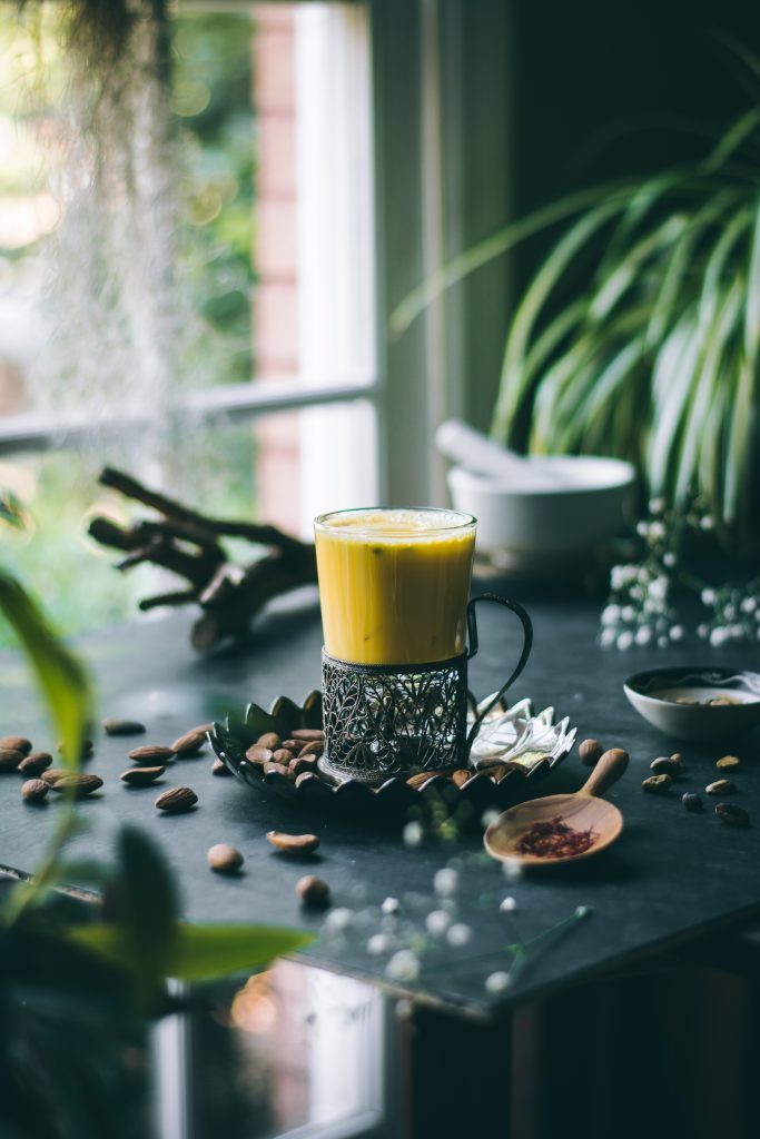 Saffron and cardamom infused almond milk in a Russian tea glass on a table by a window