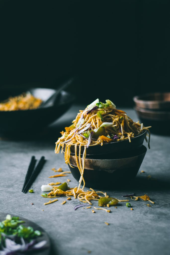 An overflowing bowl of Scrambled Tofu Curry Noodles