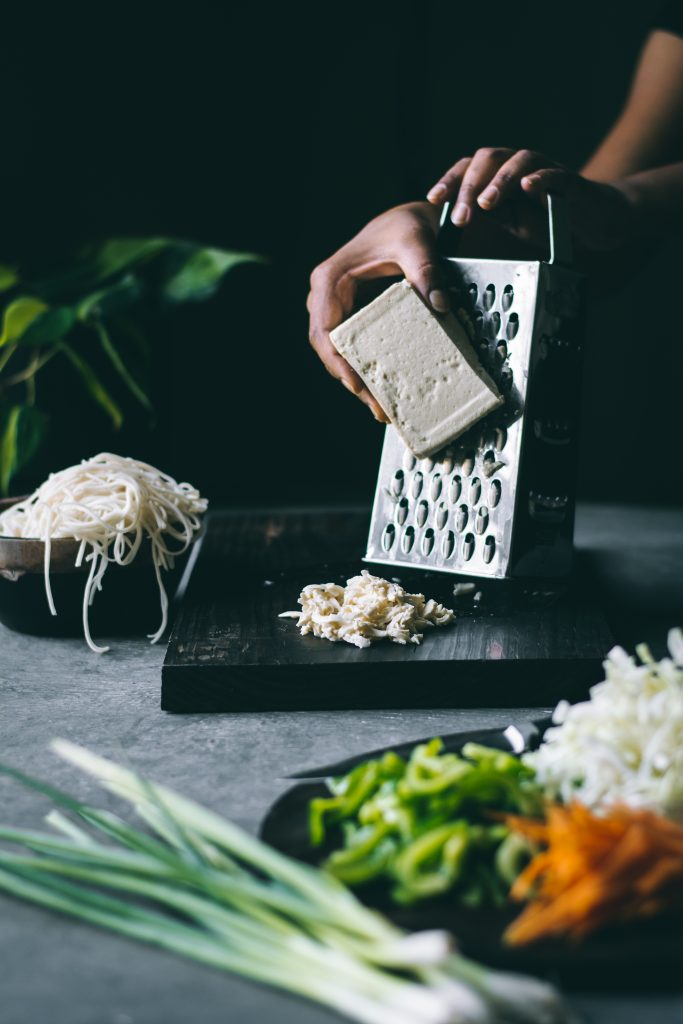 Hands grating tofu on a box grater on a table full of stir-fry ingredients