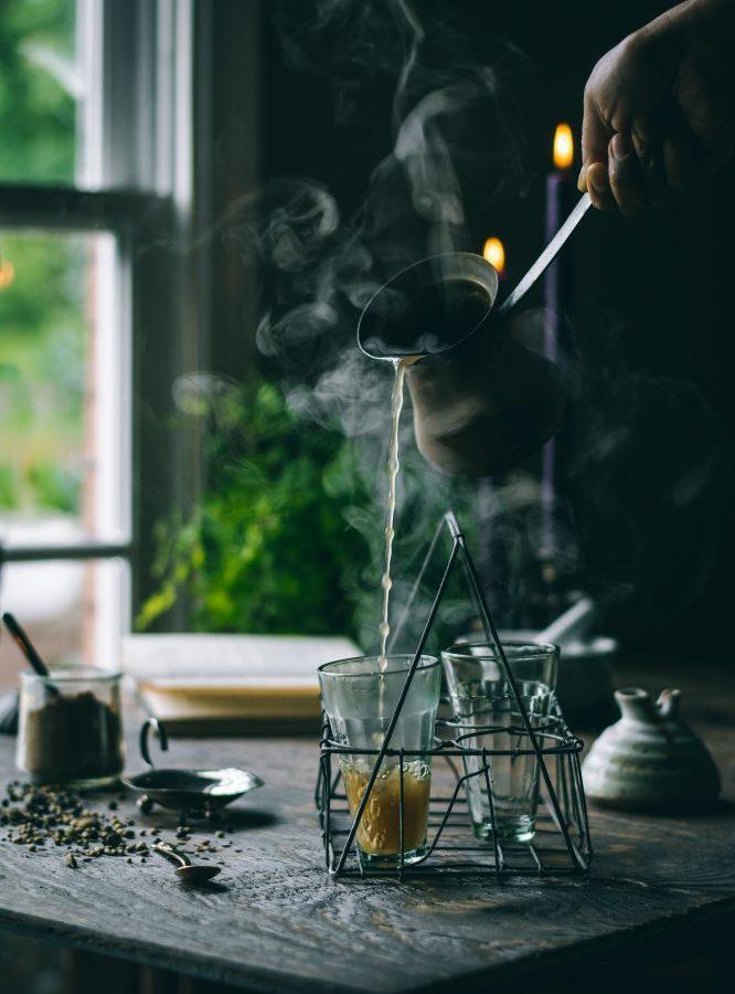 Steamy Sukku Kaapi (dry ginger tea) being poured into tea glasses.
