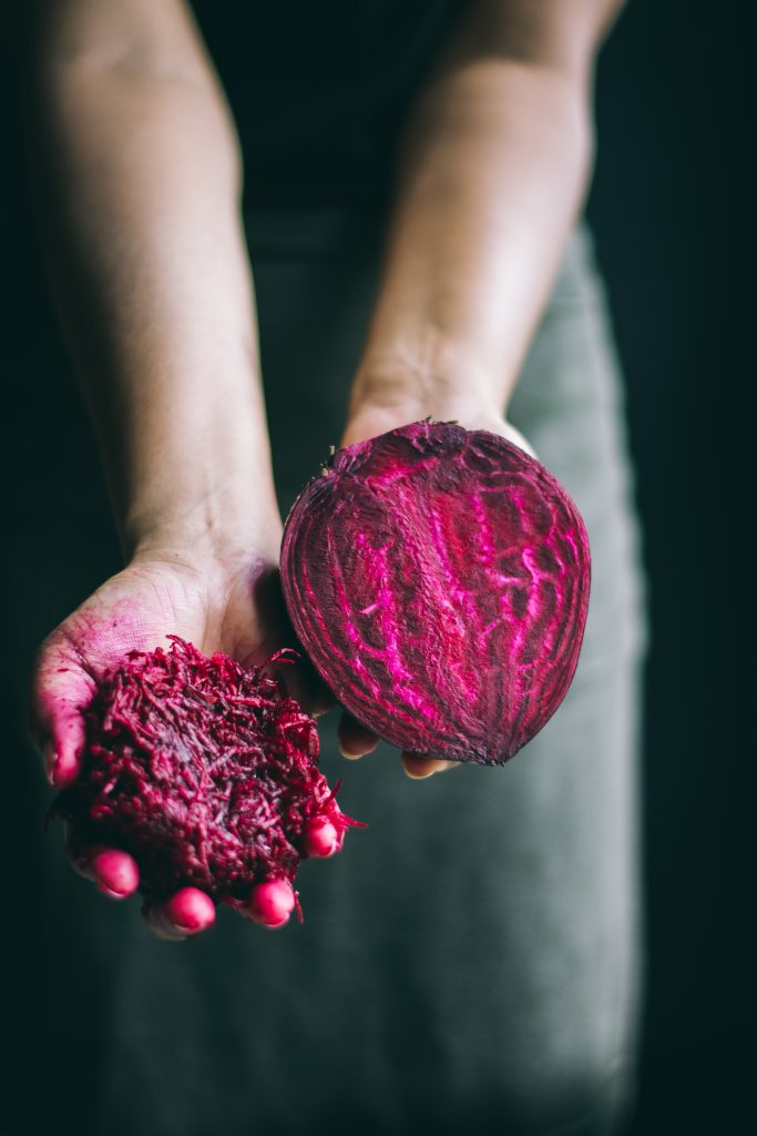 Stained hands holding beets