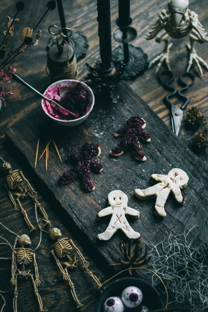 Vodoo doll cut-outs on Puff pastry sheet on a wooden table with halloween things