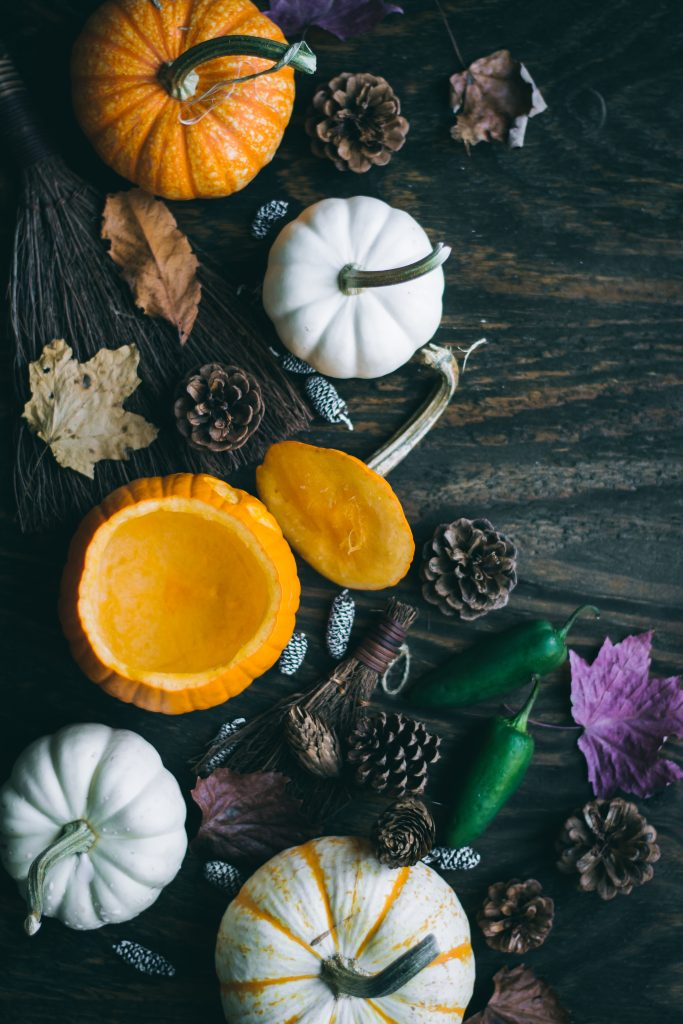 Carved mini pumpkin bowl on a table of pumpkins and pine cones and Fall leaves