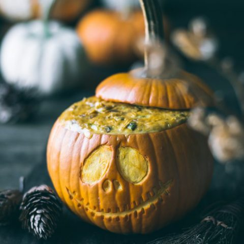 VEGAN Pumpkin Queso baked inside a mini pumkin, carved with a Jack-o-lantern face