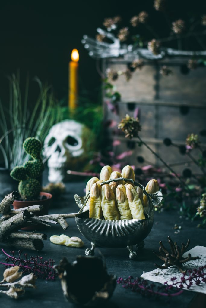 Potato Witch Fingers - a Halloween treat on a table with fog, skull, cactus, cauldron and dried branches