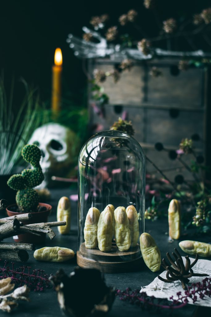 Potato Witch Fingers - a Halloween treat inside a cloche jar on a table with skull, cactus, cauldron and dried branches
