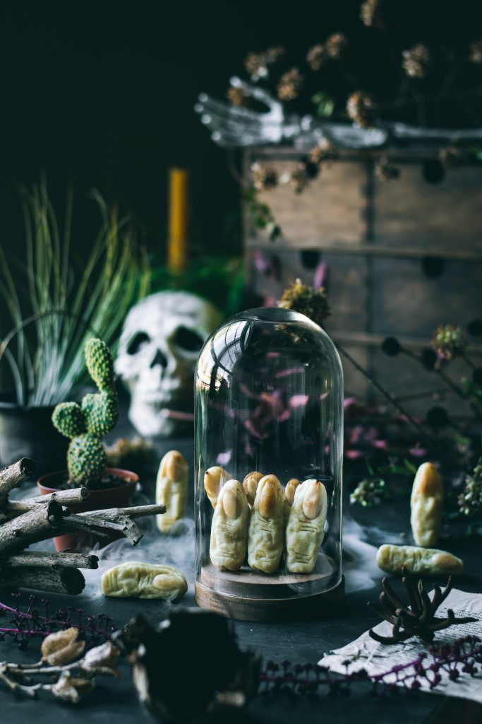 Potato Witch Fingers - a Halloween treat inside a cloche jar on a table with fog, skull, cactus, cauldron and dried branches