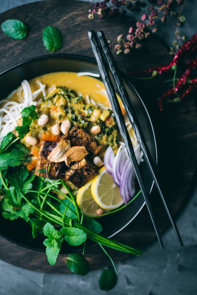 A bowl of vegan Ohn no Khao Suey with condiments and toppings.