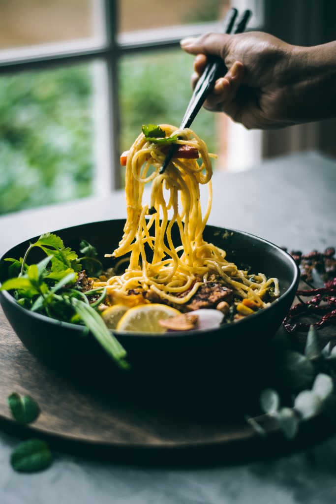 VEGAN Ohn no Khao Suey being eaten from a bowl with chopsticks