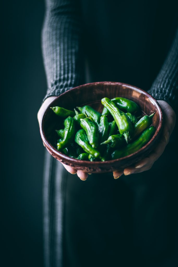Woman holding a bowl of Shishito Peppers