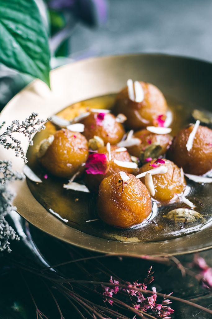 Vegan Gulab Jamun with almond slivers, saffron and cardamom