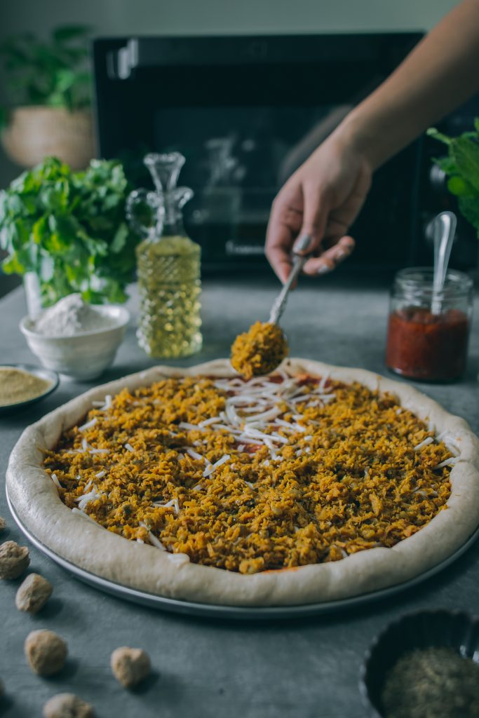 Spreading Vegan Minced Meatless Kheema made with soy on pizza dough