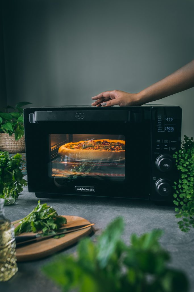 Pizza baking inside the Calphalon Performance Cool Touch Countertop Oven