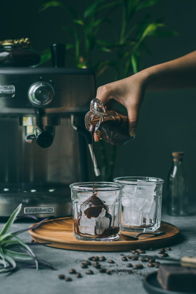 Pouring chocolate sauce on ice for VEGAN Iced Mocha Latte
