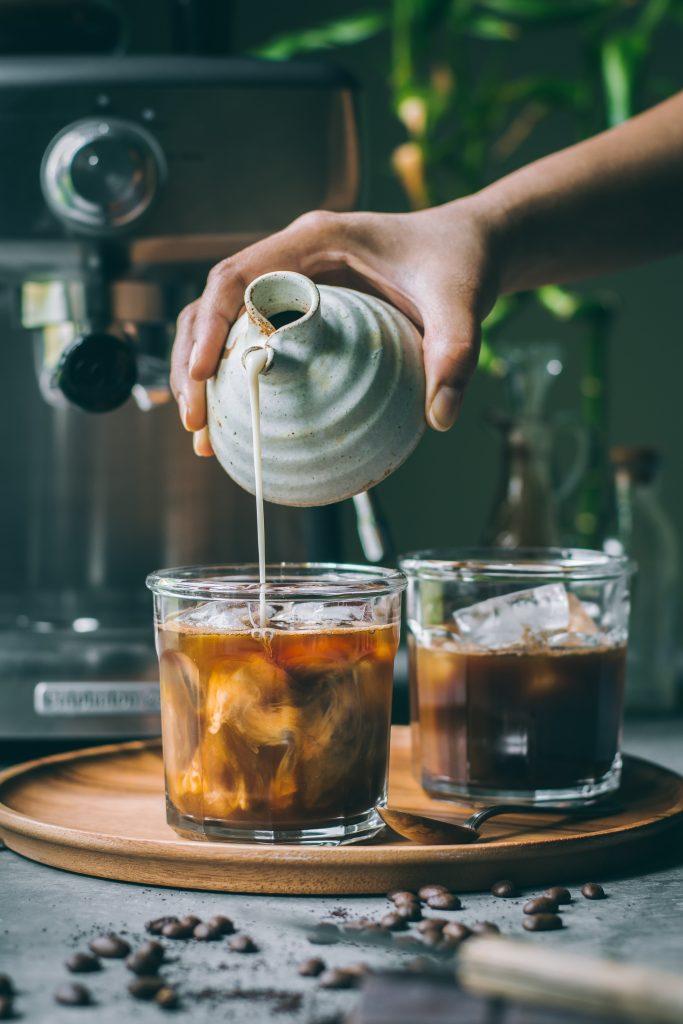 Hands pouring oat milk for VEGAN Iced Mocha Latte
