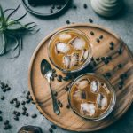 VEGAN Iced Mocha Latte on wooden plate with coffee beans strewn on table