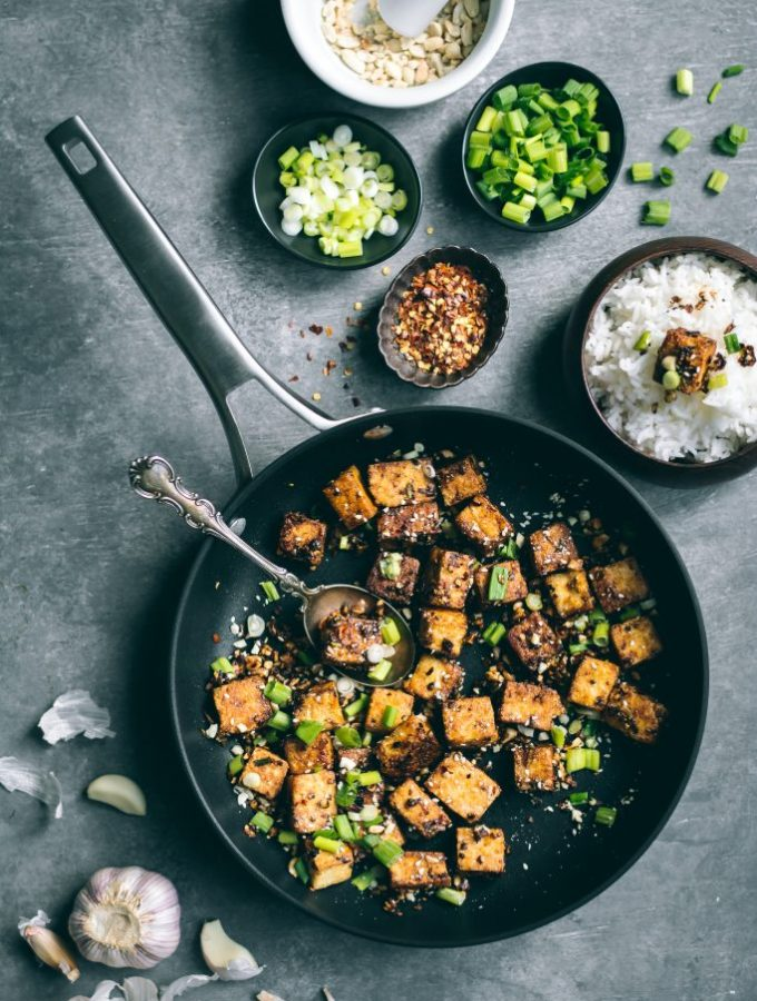 Crispy Chilli Garlic Tofu on tabletop with toppings and rice