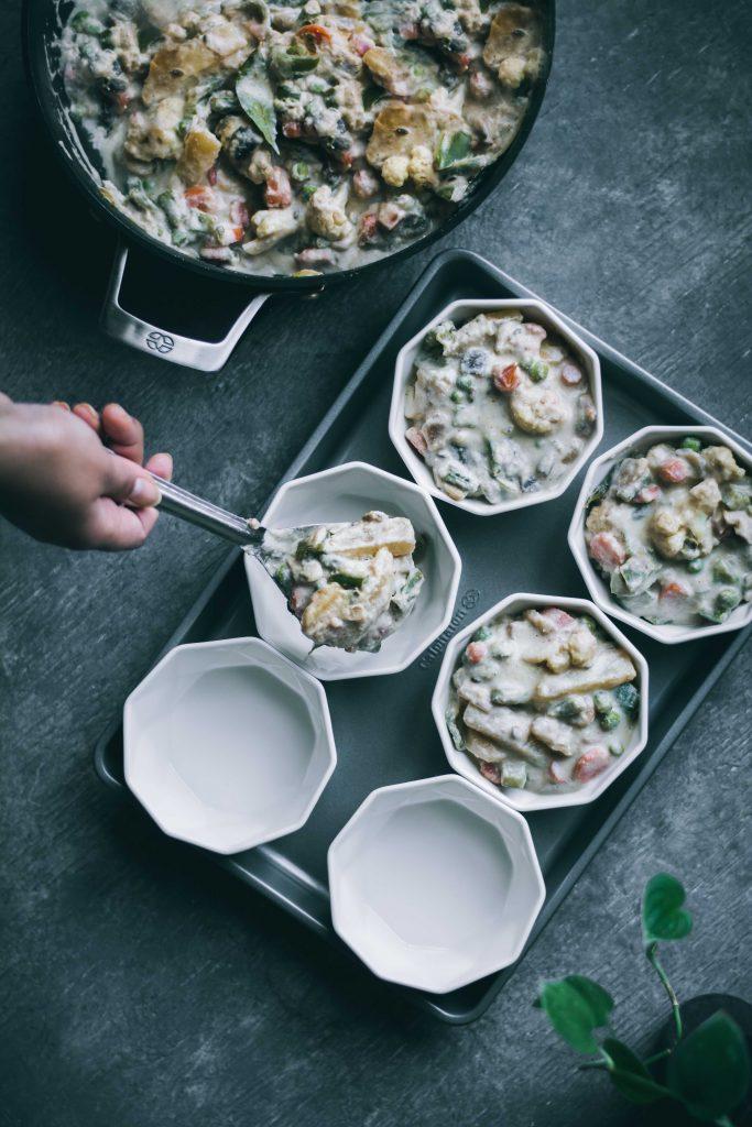 Adding the filling into inividual ramekins for VEGAN Korma Pot Pie