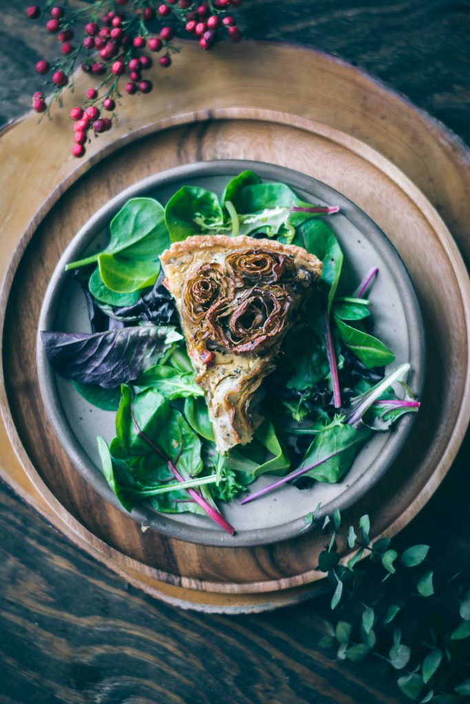 A slice of VEGAN Potato Rose Tart on a bed of salad leaves